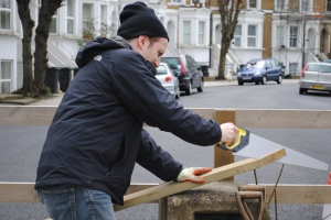 Sawing wooden fence rail Brixton Lambeth